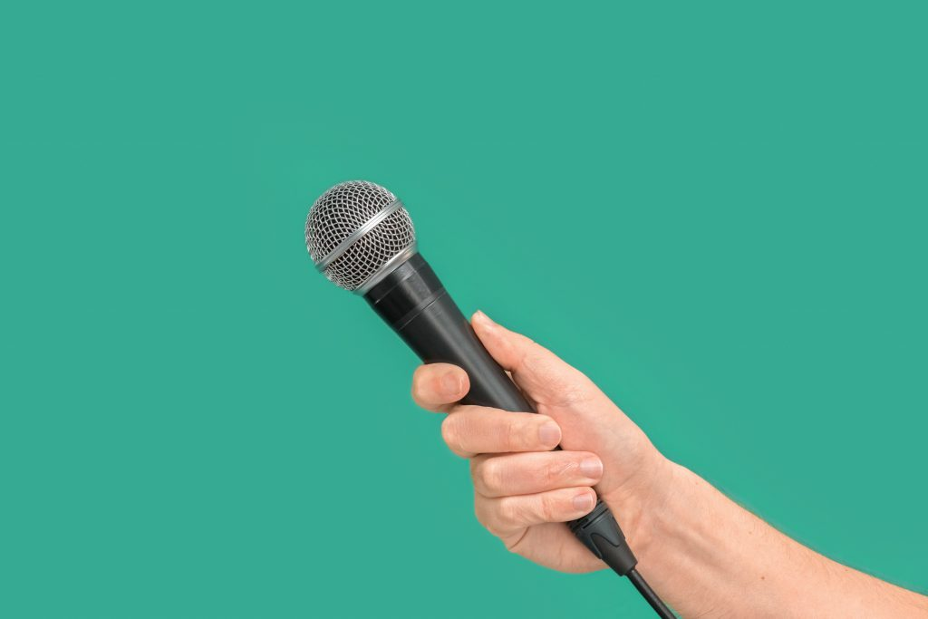 hand holding corded microphone